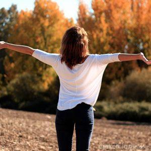 Mujer respirando con los brazos abiertos
