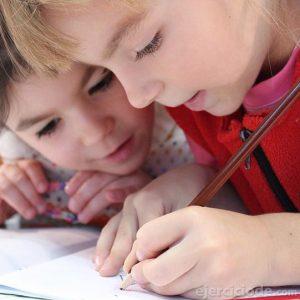 Niños escribiendo en su cuaderno de tarea