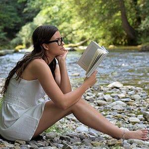 Mujer leyendo un libro cerca de un río